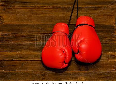 Two red boxing gloves hung on a wooden brown background empty space
