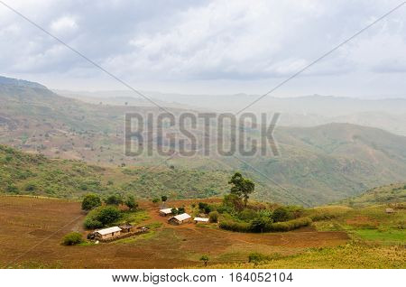 Traditional farm in the ring road region of Cameroon, Africa with mountains in the distance.