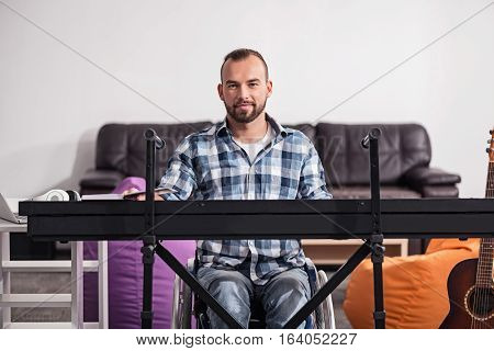 Quality leisure time. Good looking enthusiastic disabled man having quality time playing piano while spending his weekend at home