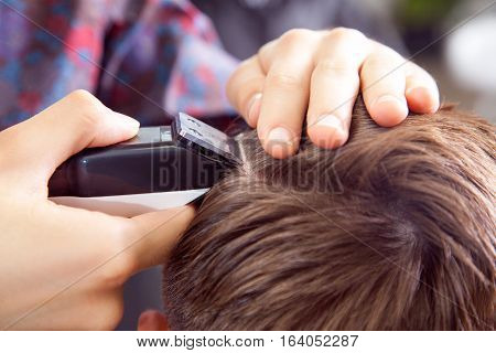 The man's haircut with clipper and razor in the barber shop