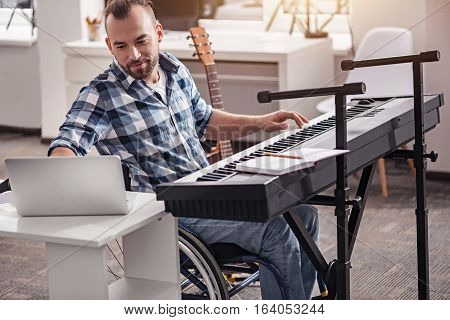 Catching harmony. Handsome enthusiastic devoted guy enjoying his free time composing beautiful melodies and recording them using his laptop while sitting in the wheelchair in a living room