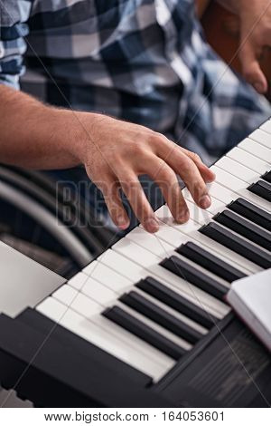 Enjoying every moment. Young devoted incapacitated man in a wheelchair experiencing new hobby of playing piano while spending his leisure time at home