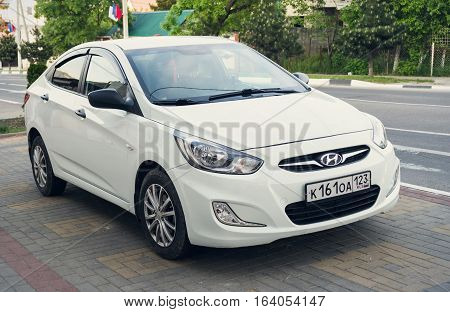 Sochi, Russia - April 29, 2016: White Hyundai Solaris parked on the street of Sochi. New korean car.