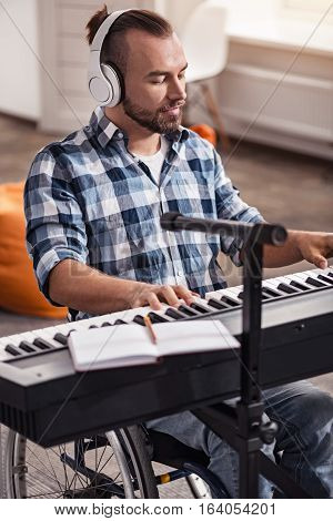 Dive in that melody. Devoted skillful disabled man working on new tracks during his leisure time while being at home and spending time in his living room