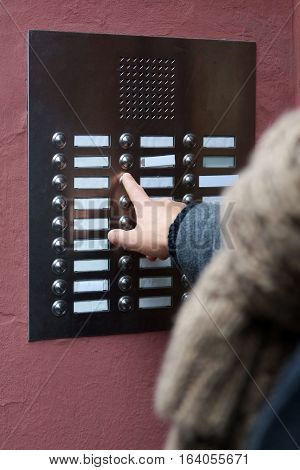 unrecognizable person ringing doorbell at apartment building. many blank nameplates.