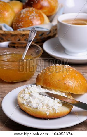 Cut bun with cottage cheese on a plate and a knife