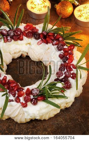 Christmas wreath made of meringue with cream pomegranate cranberry rosemary