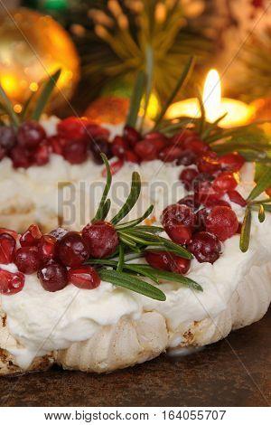 Christmas wreath made of meringue with cream pomegranate cranberry rosemary closeup