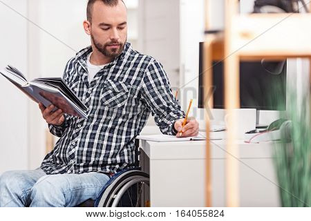 Attentive organized young gentleman in a wheelchair using his notebook writing down important phrases from a book he holding while casually sitting near the table