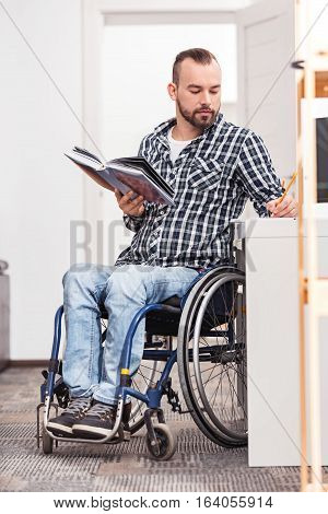 Useful notes. Concentrated handsome smart guy sitting at the table in his wheelchair and making notes while holding a book in his another hand