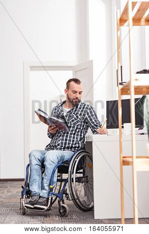 Lifelong student. Focused attractive disabled man writing down something using a pencil while working at home during the weekend