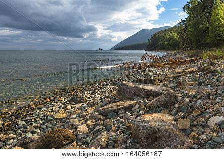 August afternoon storm clouds gathering over the rocky coast of lake Baikal.