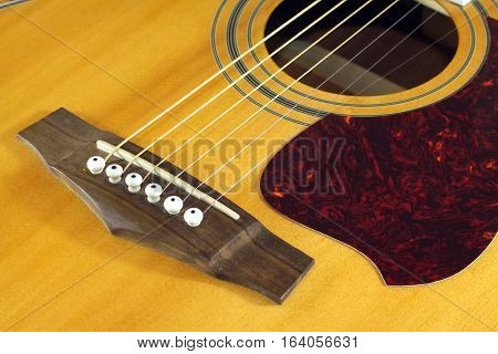 Classic acoustic six strings guitar with natural color top fragment closeup