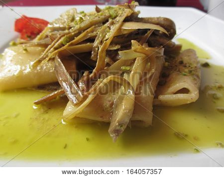 Traditional italian Paccheri pasta with artichokes and pistachios