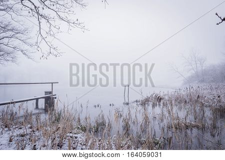 Snowy Winter Scene With Pond And Wooden Footbridge