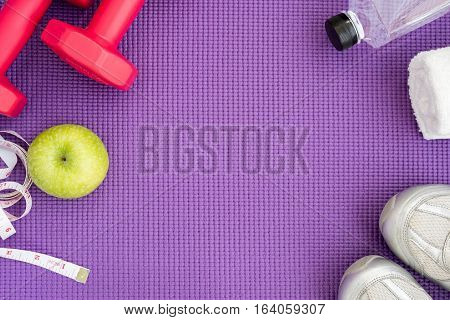 Fitness background with red dumbbells green apple sport shoes white towel water and measuring tape over violet yoga mat with copy space. Healthy and lifestyle concept