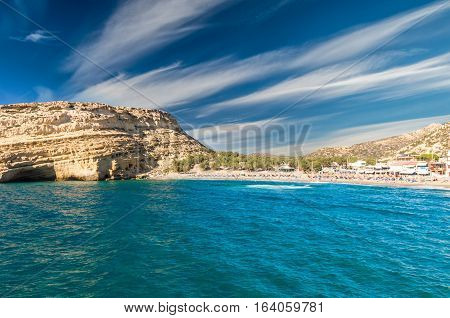 Tourists relax and bath in crystal clear water of Matala in south of Creta. There are many caves near the beach.