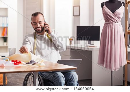 You might like this dress. Positive attractive attentive guy calling his friend talking about new project while sitting at his desk and choosing cloth