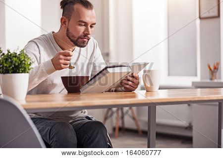Paying attention. Enthusiastic handsome intelligent guy looking through a book while eating the first meal of the day and sitting in a wheelchair at the table