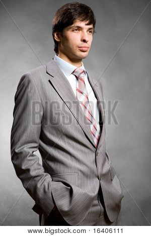 Portrait of the businessman in a grey suit. In studio.