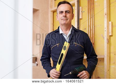 Portrait Of Male Builder With Spirit Level And Electric Drill