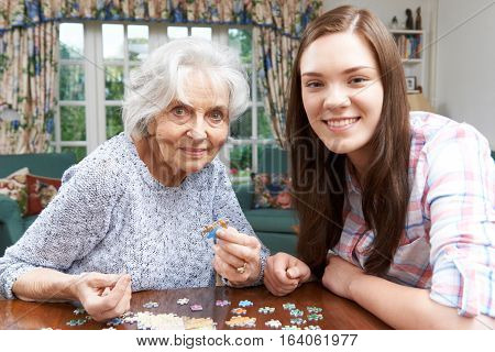 Teenage Granddaughter Doing Jigsaw Puzzle With Grandmother