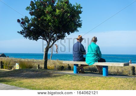 Mount Maunganui, New Zealand - December 21, 2016; Elderly couple rest and look at scenic ocean view on bench seat along Mount Maunganui ocean-beach while man appears to be walking above the water beyond beach. bare-chested man in distance practicing slack