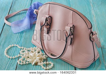 Women's accessories. Pink bag and jewelery. on a wooden background