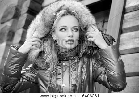 Black & White portrait of the beautiful, smiling young woman with a fur hood.
