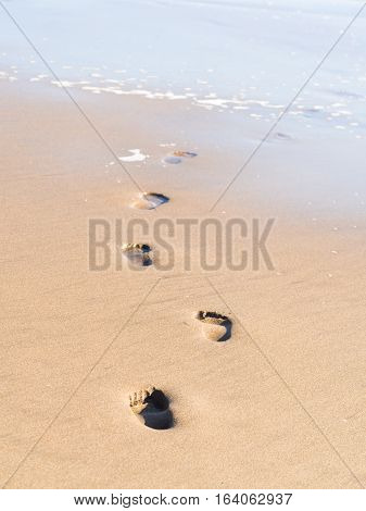 Footprints going into the sea on a beach in Namibia.