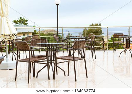Round tables with wicker chairs outside on veranda of restaurant overlooking the Cretan sea. Resort hotel Bali Rethymno Crete Greece
