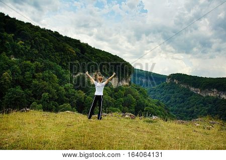 Joyful female traveler stands on the edge of abyss above vast forest territory. Beautiful girl traveling and enjoying freedom