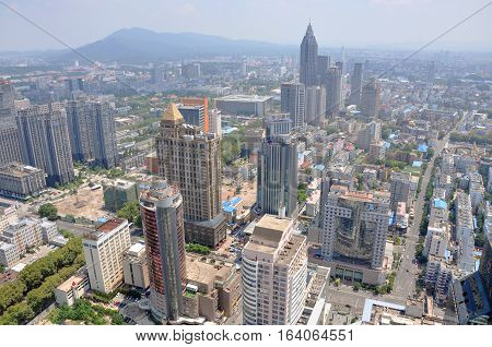 NANJING, CHINA - AUG. 6, 2012: Aerial view of Nanjing City center skyline (Northeast) and Purple Mountain, viewed from Xinjiekou CBD, Nanjing, Jiangsu Province, China.