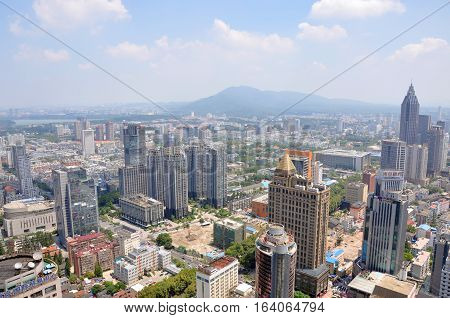 NANJING, CHINA - AUG. 6, 2012: Aerial view of Nanjing City center skyline (Northeast) with Purple Mountain and Xuanwu Lake on the far away, viewed from Xinjiekou CBD, Nanjing, Jiangsu Province, China.