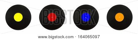 Row from four black long-play vinyl records with color labels isolated on white