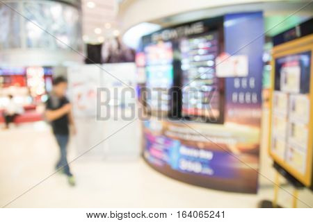 People In Cinema Lounge With Digital Display Of Movie Showtime