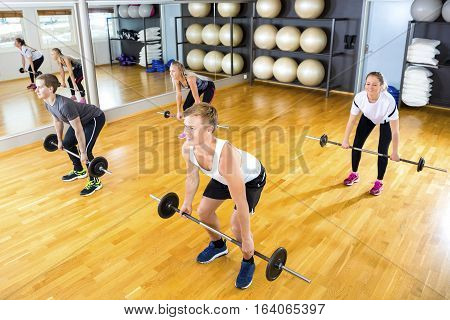 High angle view of young male and female friends exercising with barbells in gym
