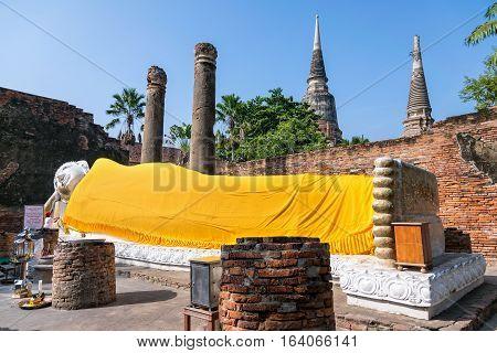 Buddha statues are white covered with yellow robe poses sleep amidst ancient ruins at Wat Yai Chai Mongkon temple in Phra Nakhon Si Ayutthaya Historical Park Ayutthaya Province Thailand