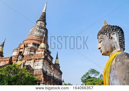 Buddha statue and ancient pagoda on blue sky background at Wat Yai Chaimongkol temple in Phra Nakhon Si Ayutthaya Historical Park Ayutthaya Province Thailand