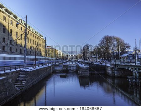 Tram in blurred motion along a canal in Gothenburg city, Sweden.