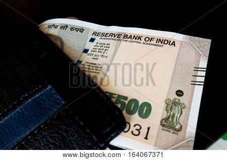 Black leather wallet with the new indian paper currency isolated on black. These new notes are still in short supply