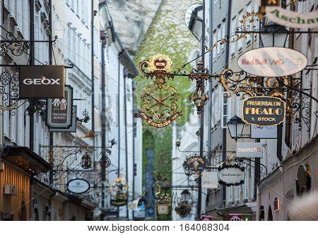 SALZBURG AUSTRIA - APRIL 29 2016: Shopping street in Salzburg -Getreidegasse with multiple advertising signs. Getreidegasse is one of the oldest streets in Salzburg