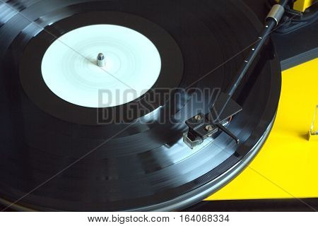 Turntable in yellow case playing a vinyl record with white label. Horizontal photo top view closeup