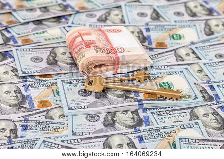 House keys and stack of five thousandths banknotes of russian roubles lying over heap of dollar banknotes