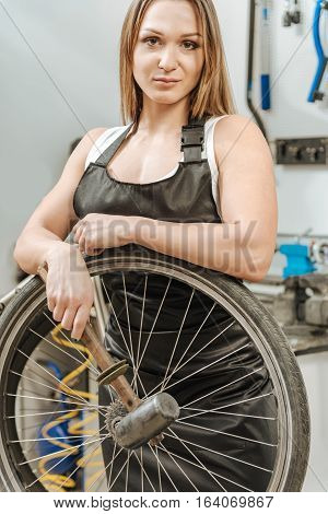 Female bodybuilder doing male job. Muscular athletic sportive craftswoman standing in the repair shop and working while taking purchase on the wheel and holding the hammer