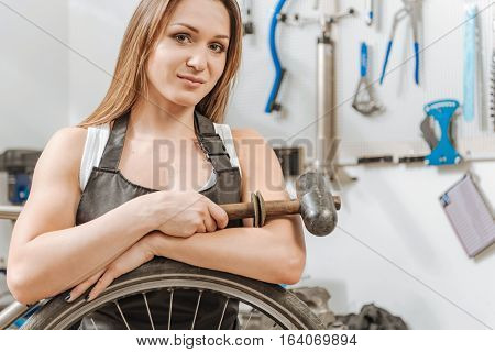 Strong woman doing hard work. Muscular athletic strong craftswoman standing in the workshop and working while touching the wheel and holding the hammer