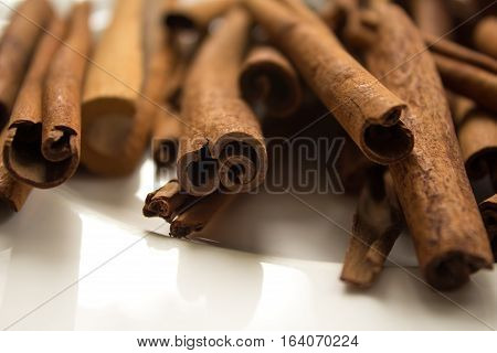 Close Up On Cinnamon Sticks On A White Plate