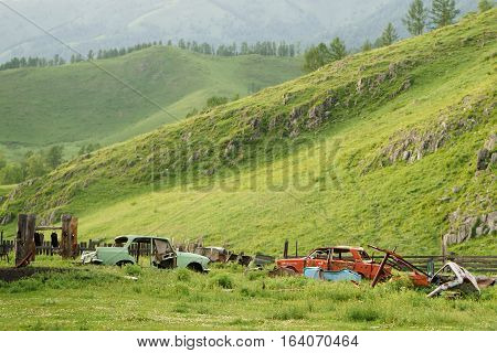 old abandoned rusty cars in the mountains Altai Russia