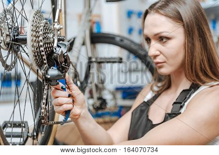 Attentive worker. Muscular strong skillful mechanic standing in the repair shop and working while fixing the chain of the bicycle