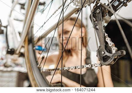 Fixing of the mountain bicycle. Concentrated watchful female technician standing in the garage near the mountain bicycle and working while repairing it